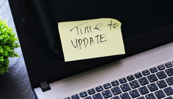 A laptop with a sticky note on it which says 'time to update'