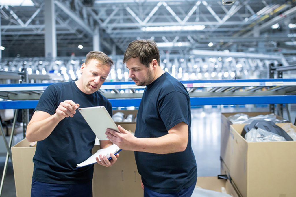 a man training his colleague about their new manufacturing crm