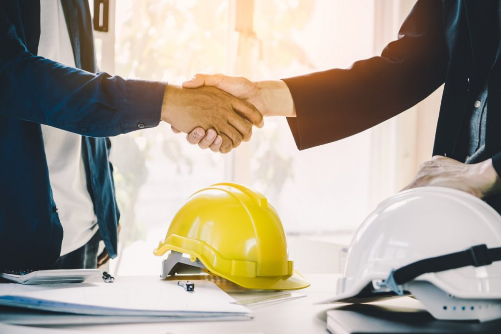 a picture of two men shaking hands to signify front and back house interaction