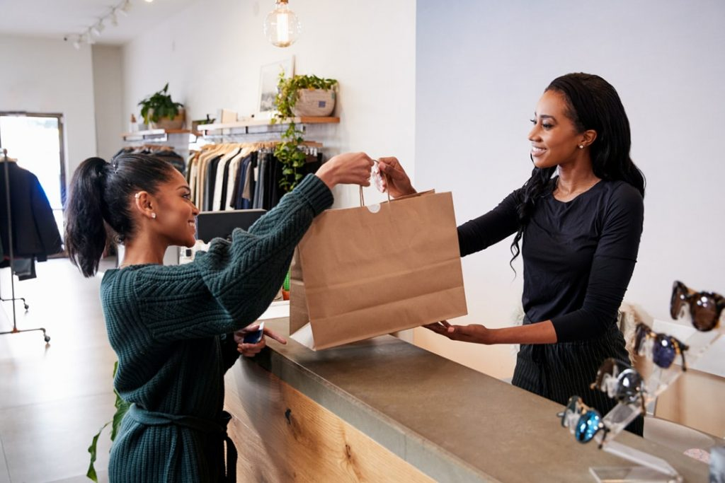 A cashier handing the paper bag to the customer
