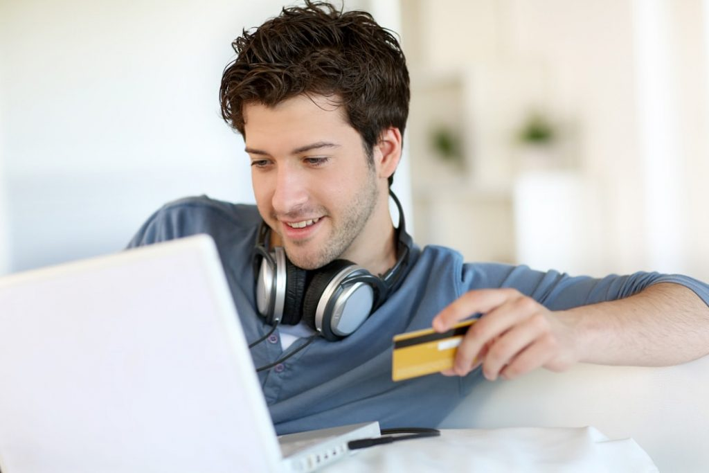 A man holding his laptop and credit card